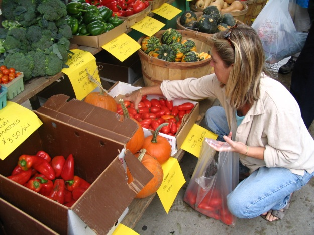 Customer shopping for tomatoes at a farmers' market.