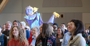 A giant NOFA puppet parades through the Winter Conference crowd.