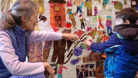 Community artist Bonnie Acker helps a Children's Conference attendee find a place on the tapestry for his piece.